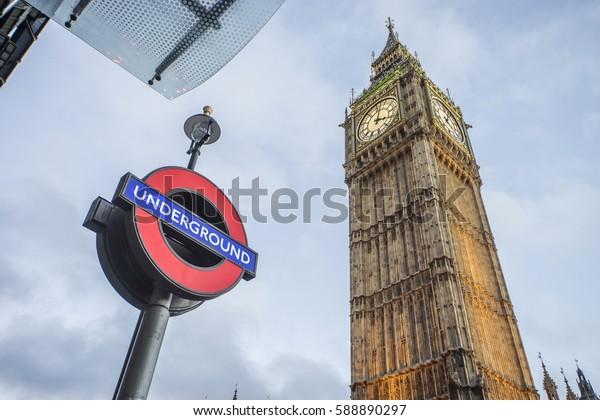 LONDON, UK -December 24, 2016: Symbols of London - Underground sign and Big Ben clock tower.