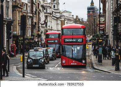 LONDON, UK - DECEMBER 24, 2017: A London black cab and a red bus waiting at traffic lights in Trafalgar Square, London.