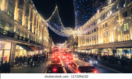 London, UK - December 26, 2016: Regent Street angels holiday lights with crowds of shoppers in London, United Kingdom