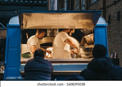 London, UK - December 29, 2019: People buying food from a Sud Italia pizza stall inside Spitalfields Market, one of the finest Victorian Markets in London with stalls offering fashion, antiques and f