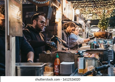 London, UK - December 29, 2019: Sellers at the stalls in Spitalfields Market, one of the finest Victorian Market Halls in London with stalls offering fashion, antiques and food. Selective focus.
