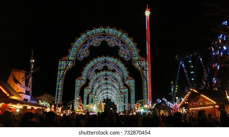 LONDON, UK - DECEMBER 5, 2015: Winter Wonderland Christmas market in Hyde Park, London, England. Colorful, illuminated arches light the entrance on a dark winter night.