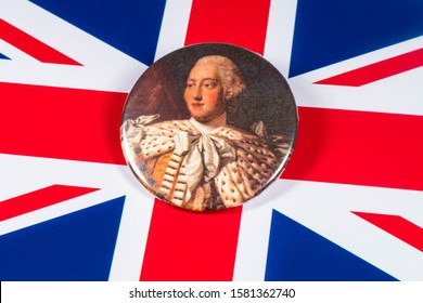 London, UK - December 6th 2019: A pin badge with a portrait of King George III of the United Kingdom, pictured over the UK flag.