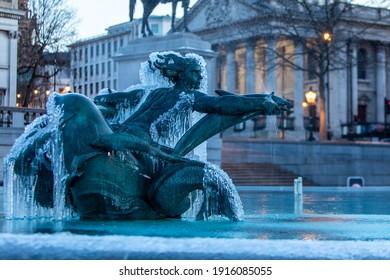 London, UK - Feb, 12 2021:  Frozen fountain statues of Trafalgar Square in London. Icicles hang off bronze water fountain