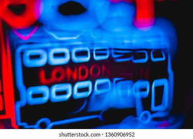 """london - UK - Feb 2019 : Bokeh light artefacts faded blurry background of a text """" London """" in red and some blue squares around it , some how look like a double-decker bus"""