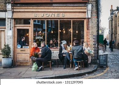 London, UK - February 03, 2019: People sitting outside S. Jones cafe on Erza Street, relaxing after visiting Columbia Road Flower Market, a street market in East London that is open every Sunday.