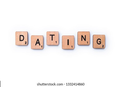 London, UK - February 13th 2019: The word DATING, spelt with wooden letter tiles over a white background.