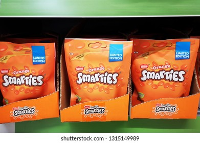 London, UK: February 16, 2019: Limited edition orange flavored smarties packets in a supermarket. Nestlé is the world's largest food company.