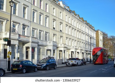 London, UK - February 2 2019: Street view of Lupus street, Pimlico, traditional white townhouses, red London double decker bus driving by, early evening sun -Image