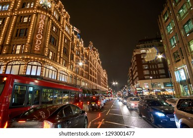 LONDON, UK - FEBRUARY 2017: Exterior view of Harrods Department Store in London at night during Winter period. Night traffic street scenery in a typical rainy day in United kingdom