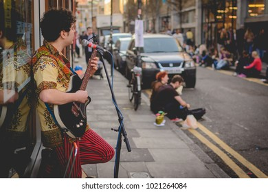 London, UK - February 2018. Street musician playing the guitar in Brick Lane.