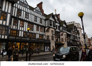 LONDON, UK - FEBRUARY 22, 2020: Taxi and shoppers passing by exterior of Liberty shopping mall, one of the oldest department stores in the city.