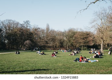 London, UK - February 23, 2019: People walking inside Holland Park, London, on the hottest spring day. Holland park is the largest park in Kensington and Chelsea borough with 22.5 hectares of gardens.