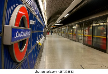 London, UK - February 26, 2014: Picture of the platform of London Bridge Underground station, with a train coming into the station and travelers in the back ground.