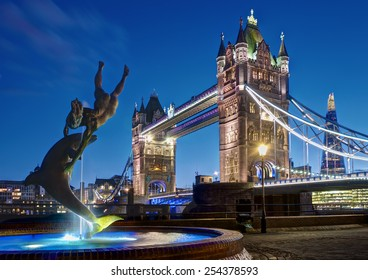 London, UK - February 26, 2014: Picture Tower Bridge with the Girl with a Dolphin sculpture by David Wynne in the foreground
