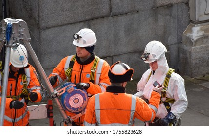 London, UK. February 26 2020. Three male and one female British water company workers / engineers working on an underground water mains pipe in Central London.