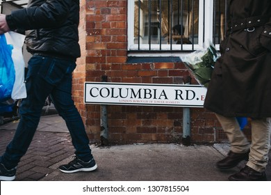 London, UK - February 3, 2019: People walking past Columbia Road street name sign with purchases made at Columbia Road Flower Market, a street market in East London that is open every Sunday.