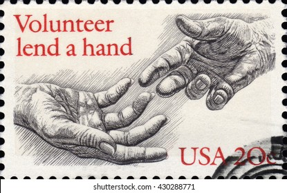 London, UK, February 5 2011 - Vintage 1983 United States of America cancelled postage stamp  showing an image of two engraved hands with a slogan saying volunteer lend a hand