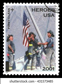London, UK, February 5 2012 - Vintage 2001 United States of America cancelled postage stamp  showing the fire department heroes of the September 11 terrorist attack raising the Stars