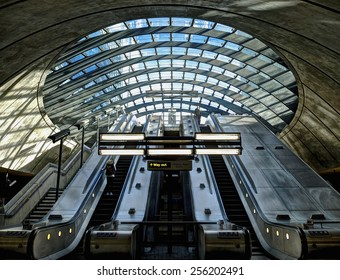 LONDON, UK - February 8, 2014: Interior shot of Canary Wharf Underground Station. The usually busy underground station on a quiet Saturday morning with two unidentified travellers on the escalators.