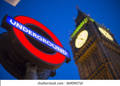 LONDON, UK - JAN 16, 2016: Big Ben Clock Tower at city of Westminster at night with the famous red/blue Underground sign on January 16, 2016 in London, England, UK.