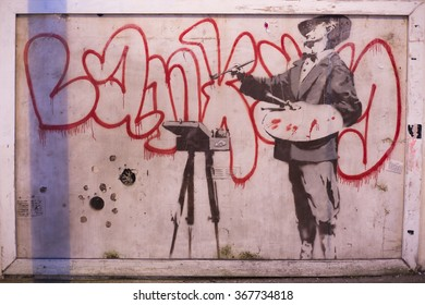 """LONDON, UK - JAN 25, 2016: Bansky's """"Nob Artiste - french painter"""" Graffiti in London. Banksy is a graffiti artist, political activist. He is one of the most popular street artist in the world."""
