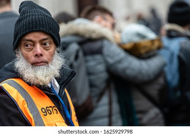 London, UK - January 1, 2020:  A man with a gray beard, a hat in his head and a reflective vest is watching  the London New Years Day Parade 2020