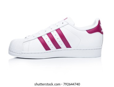 LONDON, UK - JANUARY 12, 2018: Adidas Originals Superstar red shoes on white
