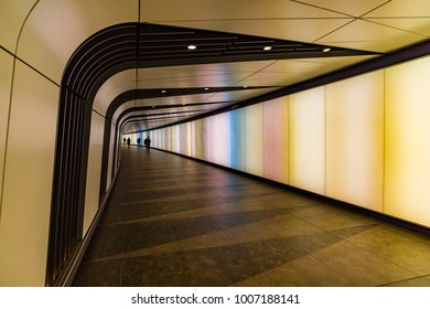 LONDON, UK JANUARY 19, 2018: People walking past a Light Wall at King's Cross, London UK. The art wall made of LED lights is a pedestrian tunnel connecting King's Cross to St Pancras Square.