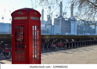 London, UK - January 19 2019: Iconic bright red phone booth with Battersea Power Station and Santander bikes in the background