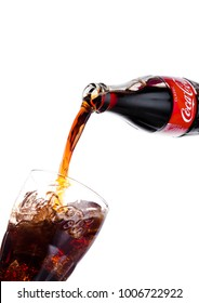 LONDON, UK - JANUARY 20, 2018: Pouring Coca Cola soda drink from bottle to glass on white background. The drink is produced and manufactured by The Coca-Cola Company.
