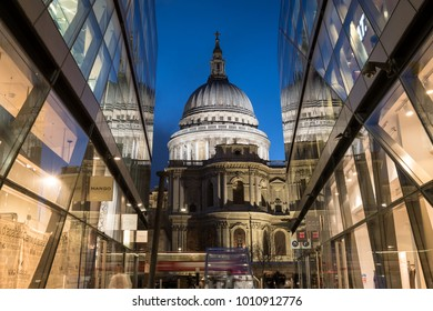 London UK. January 2018. Closeup view of the dome of St Paul's Cathedral. Dome is illuminated at night and reflects in the glass facades of the buildiings at One New Change opposite.