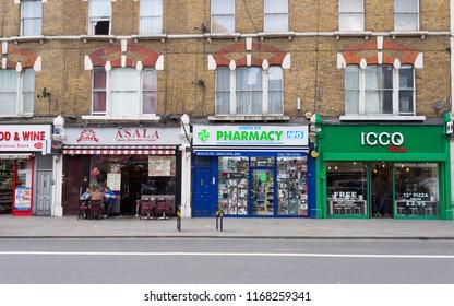 London, UK - January 2018. Local shops, pharmacy and restaurants take away in Camden High Street, North London, UK