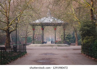 London, UK - January 21 2019: Battersea Park's Victorian bandstand during golden hour on a winter's morning. In front of the bandstand you can see some of the green parakeets which live in the park.