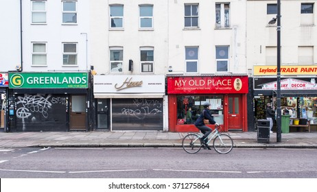 London, UK - January 24 2016:  Typical street with small independent retail shops in London East End. Cyclist passing by on the road.