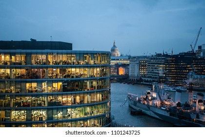 London, UK - January 31 2013: people work in a busy modern office building at dusk. Full-time employees in the UK work longer hours than the EU average, according to the Office for National Statistics
