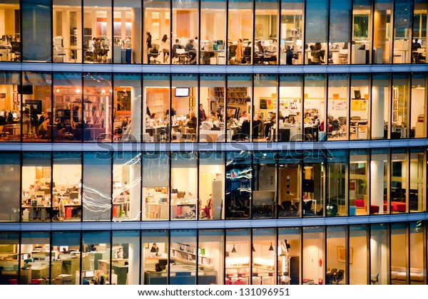 London, UK - January 31, 2013: people work in an office building at night. Windows interior. Concept for employment, business, corporate, working,brexit, business people, modern life, busy people