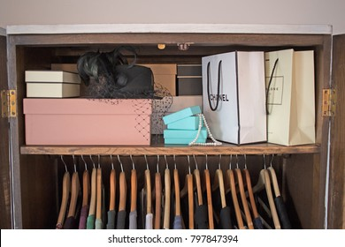 London, UK - January 6, 2018: Designer bags and shoe boxes stored on a shelf in a wooden wardrobe