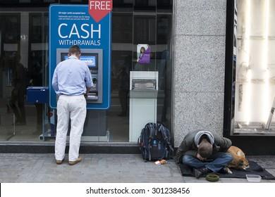 LONDON, UK - JULE 29 2015: Street beggar with dog begging for money near cash mashine. London. UK