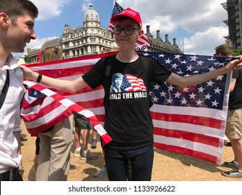 London, UK - July 13 2018: Pro Trump Protester demanding to  build the wall, with a MAGA hat and a US flag at the #makesomenoise rally in central London