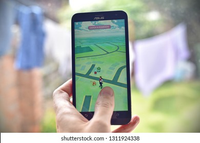 London, UK - July 14, 2016: A gamer uses a smartphone to play Pokemon Go. The worldwide hit Nintendo app has seen been the company's shares increase by 50% with millions of downloads since release.