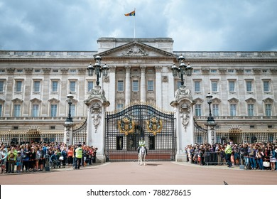 LONDON, UK - July 14, 2017: A security guard was standing in front of the main gate of Buckingham Palace to control crowded people before traditional changing of the Guards ceremony began.
