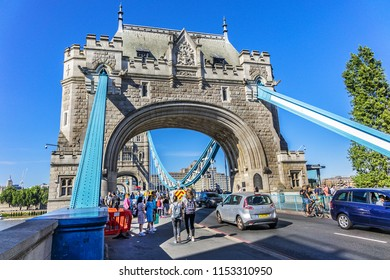 LONDON, UK - JULY 14, 2018: Tourists walk on Tower Bridge. Tower Bridge over River Thames - iconic symbol of London. Tower Bridge is close to Tower of London, from which it takes its name.