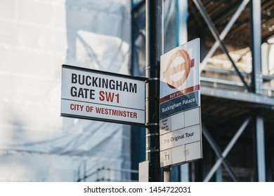 London, UK - July 15, 2019: Street name  sign for Buckingham Gate and bus stop sign for Buckingham Palace, the London residence and administrative headquarters of the monarch of the United Kingdom.