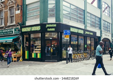 London / UK - July 16, 2019: people walking past the jamaican cuisine restaurant Healthy Eaters in Brixton; which is a district of South London, within the London Borough of Lambeth