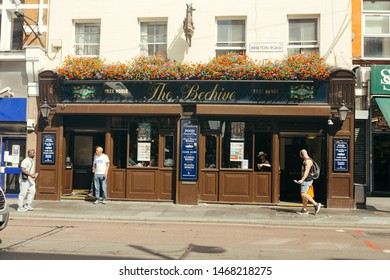 London, UK / July 16 2019: people walking past the Beehive pub on Brixton Road in London, UK. Pubs are the big part of British culture