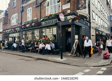 London, UK / July 16 2019: people seating at the tables outside the Prince of Wales Pub on the Longmoore Street in Pimlico, London, UK. Pubs are the big part of British culture