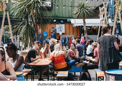 London, UK - July 16, 2019: People at the tables inside Pop Brixton, event venue and the home of a community of independent retailers, restaurants, street food startups and social enterprises.