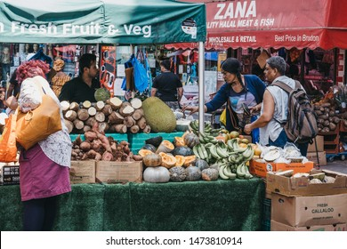 London, UK - July 16, 2019: Women buy fresh fruits and vegetables from a market stall at Brixton Market, a community market run by local traders in the centre of Brixton, south London.