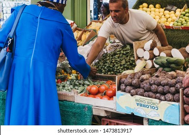 London, UK - July 16, 2019: Woman buys fresh fruits and vegetables from a market stall at Brixton Market, a community market run by local traders in the centre of Brixton, south London.